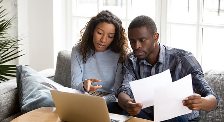 Serious African American couple discussing paper documents, sitting together on couch at home, man and woman checking bills, bank account balance, terms of contract, mortgage, loan agreement