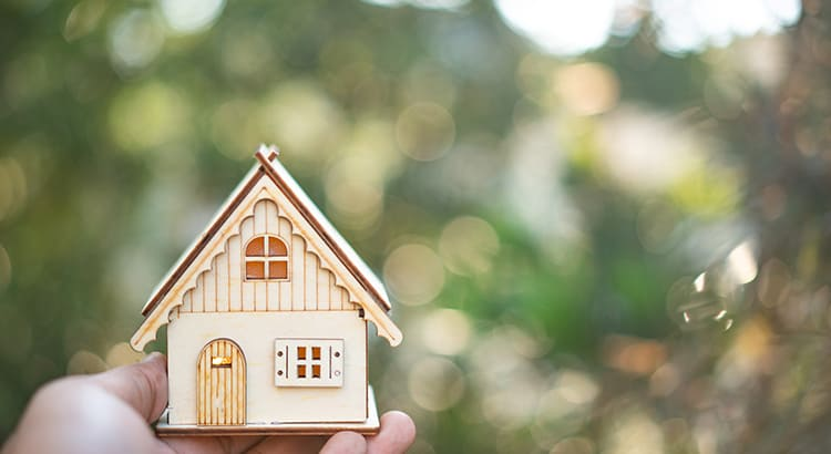 model of house as symbol on sunny background