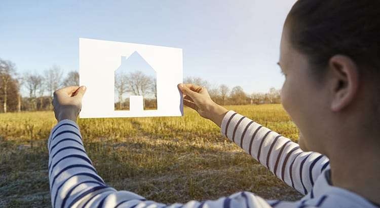 Woman standing in rural setting, holding out paper with cut-out of house