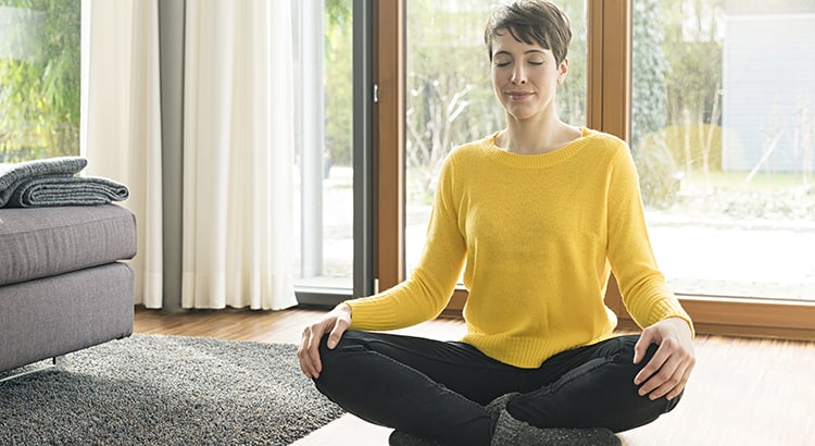 Portrait of woman sitting on the floor of living room meditating